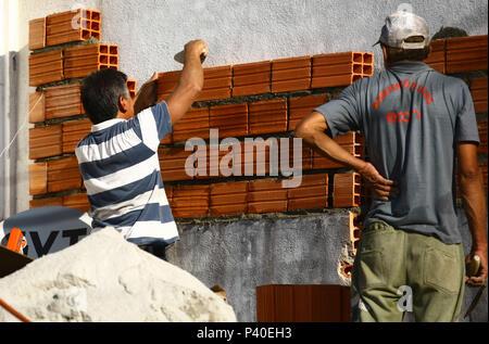 Pedreiros em construção levantando parede de tijolos.