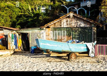 Barco sobre a areia em frente a rancho de pescadores na Praia da Daniela. Florianópolis, Santa Catarina, Brasil. - Stock Photo