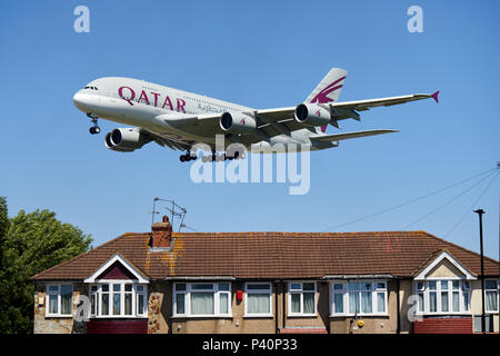 A Qatar Airways Airbus A380-800 aircraft, registration number A7-API, flying low over houses as it descends for a landing at Heathrow Airport, London. - Stock Photo