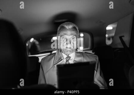 Businessman with a digital tablet sitting in the back seat of a car - Stock Photo