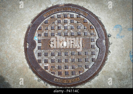 close up of a metal storm drain cover in the USA - Stock Photo