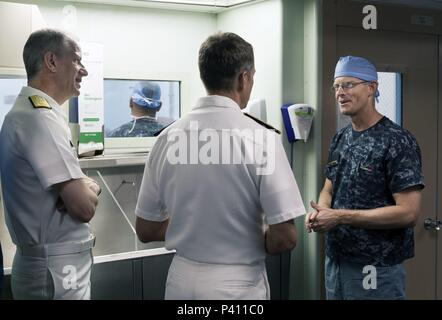 Photograph of three Navy officers, one wearing surgical scrubs, speaking with each other onboard the hospital ship USNS Mercy, in the waters off of Nha Trang, Vietnam, May 23, 2018. () - Stock Photo