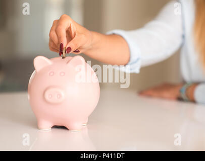 Beautiful young woman hands holding a coin investing in to a piggy bank at home. Business concept. - Stock Photo