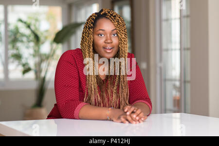 African american woman sitting at home scared in shock with a surprise face, afraid and excited with fear expression - Stock Photo