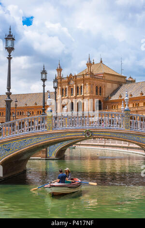 Seville Plaza de Espana, a young couple row towards an azulejo decorated bridge on the boating lake in the Plaza de Espana, Seville, Andalucia,Spain. - Stock Photo