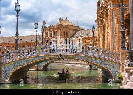 Seville Plaza de Espana, view of a colorful azulejo decorated bridge spanning the boating lake in the Plaza de Espana in Seville, Andalucia, Spain. - Stock Photo