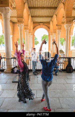 Flamenco Spain, two flamenco dancers perform under the colonnade in the Plaza de Espana on a summer afternoon in Seville (Sevilla), Spain. - Stock Photo