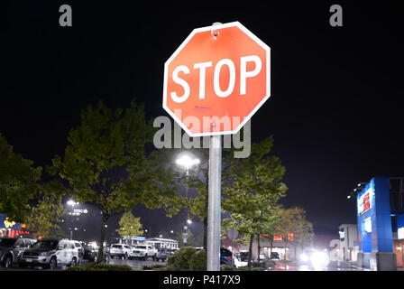 Coquitlam, BC, Canada - May 08, 2018 : Motion of stop sign in front of parking lot at raining night - Stock Photo