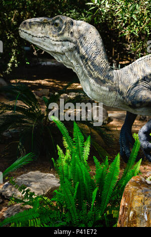 A resin T-Rex lurks among the fern gardens in a Jurassic environment - Stock Photo