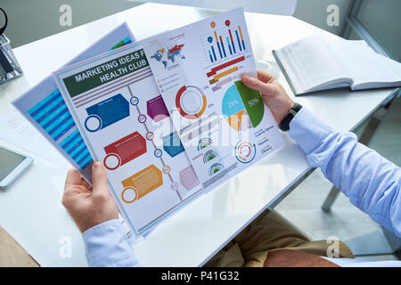 Crop businessman working with graphics - Stock Photo