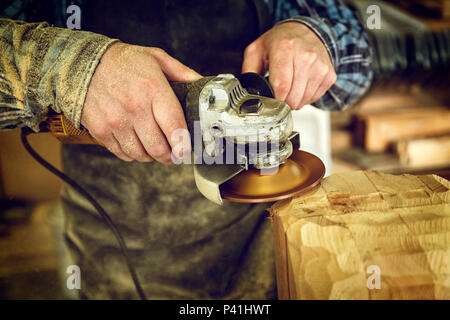 Close up experienced carpenter in work clothes and small buiness owner processes the board with an angle grinder on the table is a hammer and many too - Stock Photo