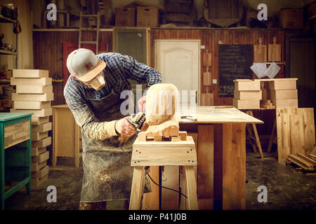 Experienced carpenter in work clothes and small buiness owner working in woodwork workshop, processes the board with an angle grinder on the table is  - Stock Photo