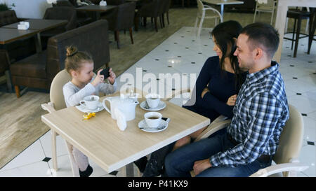 Little modern girl takes photos of her lovely parents in cafe. - Stock Photo