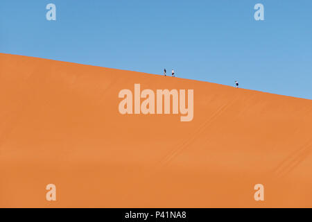 The red sand Dune 45 is popular for climbing by tourists at Sossusvlei, inside the Namib-Naukluft Park in Namibia. - Stock Photo