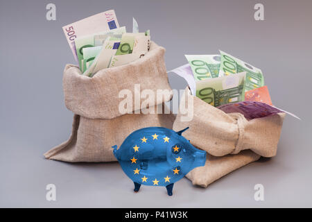 Two money bag with euro and glass piggy bank with Flag of European Union on gray - Stock Photo