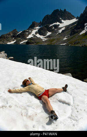 A woman makes snow angles in the August snow around Cecil lake, our highest lake at 10,239 in the Ansel Adams Wilderness of the High Sierra mountains. - Stock Photo