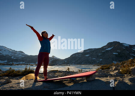 A woman backpacker does yoga at camp in the granite around Lake Aloha in the Desolation wilderness hike in south lake tahoe, California, USA. - Stock Photo