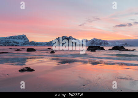 Sunset on Haukland Beach. Lofoten, Norway. Snowy mountains and rocks in the sea with orange sky. - Stock Photo