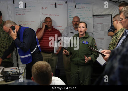 160607-N-DC740-004 OAK HARBOR, Wash. (June 7, 2016) Lt. Cmdr. Kari Imperatore, assistant operations officer, Naval Air Station Whidbey Island (NASWI), briefs members of the emergency management team in an emergency operations center in Mobile Tactical Operations Center Four during an earthquake and tsunami scenario of Citadel Rumble 2016 at NASWI. Citadel Rumble is an integrated disaster response and recovery exercise for shore-based commands to exercise and validate their emergency management plans.  (U.S. Navy photo by Mass Communication Specialist 2nd Class John Hetherington/Released) - Stock Photo