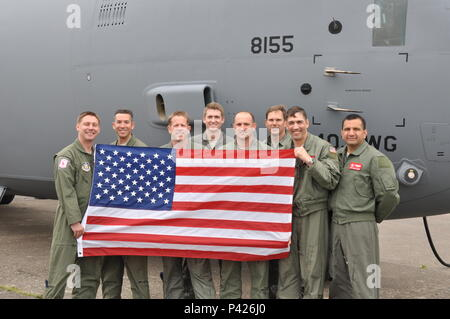 Members of the 815th Airlift Squadron pose with a U.S. flag next to the C-130J.  The 815th AS provided aerial transport of U.S. and French Airborne troops for the scheduled massive parachute drops.  More than 380 service from Europe and affiliated D-Day historical units are participating in the 72nd anniversary as a part of Joint Task Force D-Day 72.  The Task Force, based in Sainte-Mère-Église, France, is supporting local events across Normandy, from May 30 - 6 June, 2016 to commemorate the selfless actions by all of the allies on D-Day that continue to resonate 72 years later.  (U.S. Air For - Stock Photo