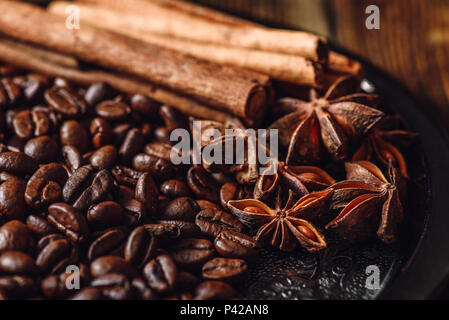 Coffee Beans with Cinnamon Sticks and Chinese Star Anise on Metal Plate. - Stock Photo