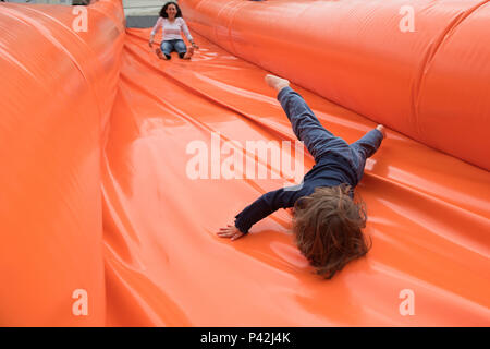 Kid and mother slide on a giant inflatable slider - Stock Photo