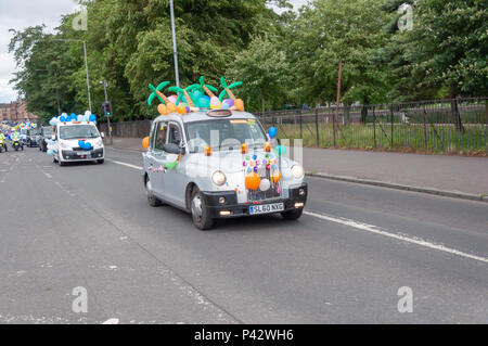 Glasgow, Scotland, UK. 20th June, 2018. The 73rd Glasgow Taxi outing is an annual event where over 100 taxi drivers of the city dress up in fancy costumes, decorate their taxis and take more than 300 children with special needs on a day trip to the seaside town of Troon. Pictured a taxi on the road decorated with colourful balloons. Credit: Skully/Alamy Live News - Stock Photo