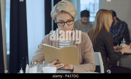 Sunday morning lifestyle scene of young hipster woman reading notes on her notebook in cafe - Stock Photo