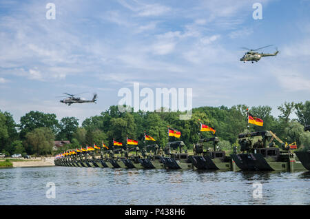 Helicopters fly over troops on a hasty bridge during a bridge crossing operation in Chelmno, Poland, June 8, 2016. Multinational forces coordinated, assembled and then traversed a bridge composed of German and British M3 Amphibious Rigs, allowing vehicles to cross the Vistula River as a part of Exercise Anakonda 2016. The Polish-led exercise is a collective training effort to reinforce interoperability and strengthen bonds between NATO allies and partners, ensuring collective peace and security in the region. - Stock Photo