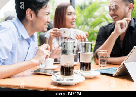 Vietnamese coffee served on the table of three friends outdoors  - Stock Photo