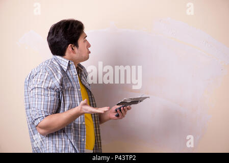 Young man applying plaster on wall at home - Stock Photo