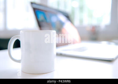 Coffee mug and laptop in office table interior - Stock Photo