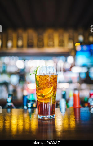 Fresh colorful exotic alcoholic cocktail with lime in the bar. Colorful gold Soft drink with lemons on the bar desk. Jagermeister Mojito Cocktail - Stock Photo