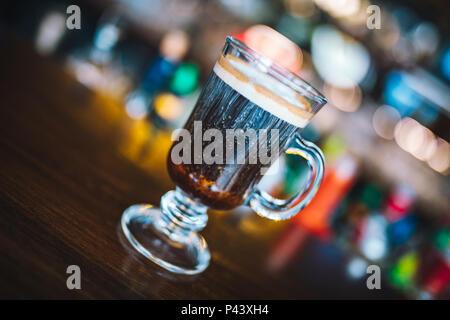Irish coffee on irish pub bar desk. Concept of St Patrick's holiday. Holiday background. Irish national day. Warm and dark tone. Blur Background