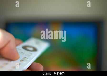 Extreme close up shot of a hand holding a television remote control and pointing it at a television set to change the channel - Stock Photo