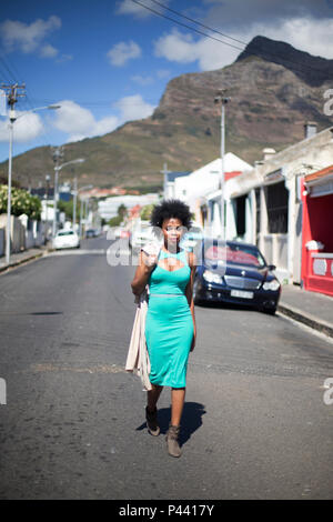 A young African model walks down a street lined with old houses - Stock Photo