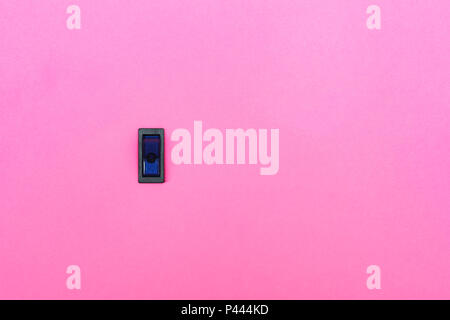 Blue toggle switch on a pink background. Abstract photo with blank empty space for free title - Stock Photo
