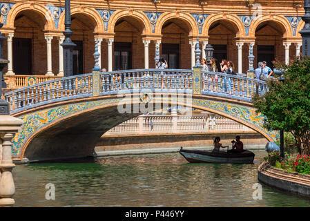 Plaza de Espana Seville, view of a bridge decorated with colorful azulejo tiles spanning a lake in the Plaza de Espana, Sevilla, Andalucia, Spain.