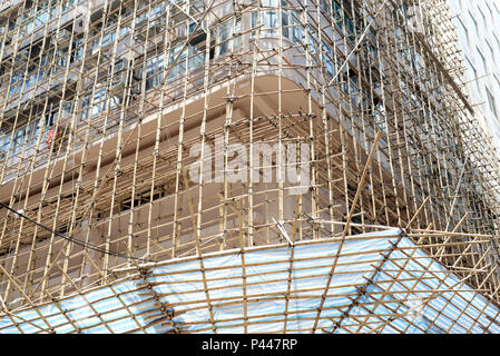 In Hong Kong and China and other parts of Asia, bamboo is often used for scaffolding for real estate construction in place of steel or iron scaffolds - Stock Photo