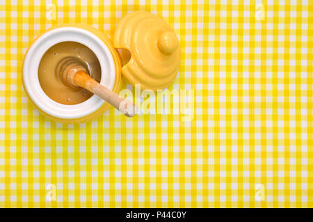 A beehive themed pot full of Manuka honey with wooden dipper on a yellow gingham background with copy space. - Stock Photo