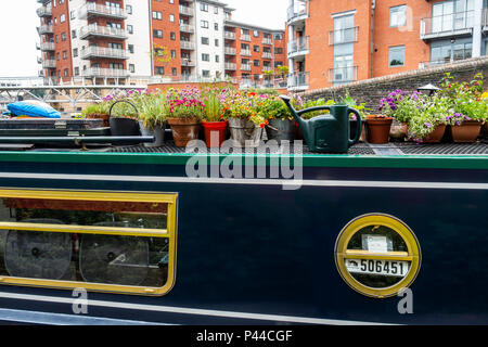 Detail of a berthed barge, with flower containers and a watering can, on a canal in front of flats /apartments  in Birmingham City Centre, England, UK - Stock Photo