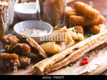 Spicy baked chicken wings, bread sticks with appetizers and sauces on round wooden Board - Stock Photo