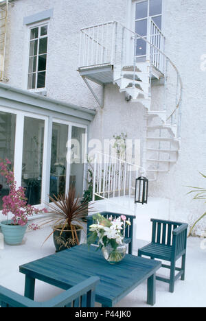 Rear elevation of house with spiral staircase to patio with painted wooden table and chairs outside glass doors - Stock Photo