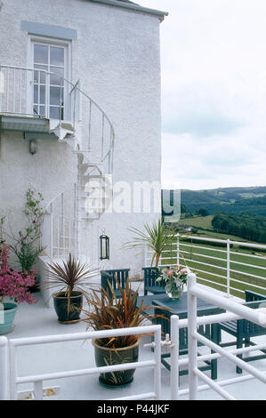 Phormium in pots nd painted wooden furniture on balcony terrace of white house with white spiral staircase - Stock Photo