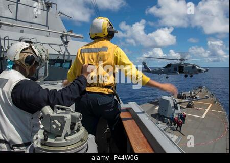 """160614-N-SU278-655  PACIFIC OCEAN (Jun. 14, 2016) – Boatswain's Mate 1st Class Terence Thompson (left) and Boatswain's Mate 3rd Class Michael Defries, assigned to the guided-missile destroyer USS Spruance (DDG 111), control an MH-60R helicopter, assigned to Maritime Strike Squadron (HSM) 49, during a vertical replenishment practice exercise on the ship's forecastle. Spruance, along with the guided-missile destroyers USS Momsen (DDG 92) and USS Decatur (DDG 73), and embarked """"Devil Fish"""" and """"Warbirds"""" detachments of HSM 49, are deployed in support of maritime security and stability in the Indo - Stock Photo"""