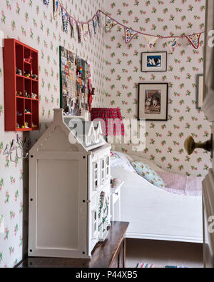 Large dollshouse in girls room with pinboard and bunting - Stock Photo