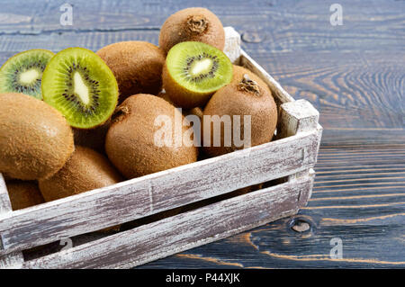 Fresh ripe kiwi fruit in a wooden box on the table. Tropical Fruit. Healthy food. - Stock Photo