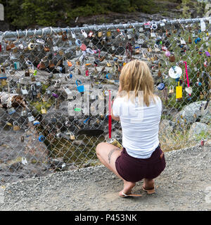 Rear view of woman attaching a lock on fence, Wally Creek, Vancouver Island, British Columbia, Canada - Stock Photo