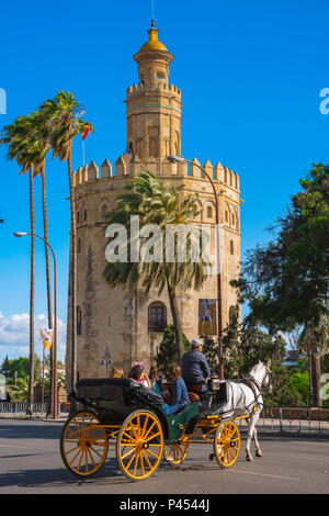 Seville Spain, tourists in a horse-drawn carriage ride past the Torre del Oro (Tower of Gold) in the old town quarter of Seville, Andalucia, Spain. - Stock Photo