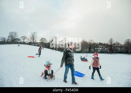 Man is out sledding in the snow with his daughters. - Stock Photo